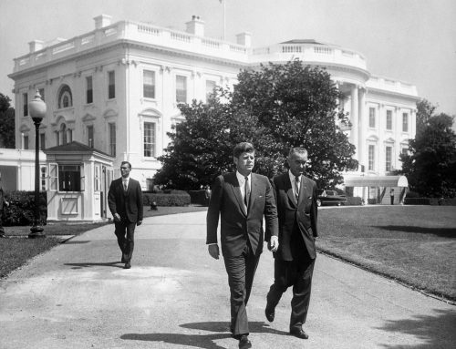 President John F. Kennedy and Vice President Lyndon B. Johnson walk across the South Lawn driveway at the White House