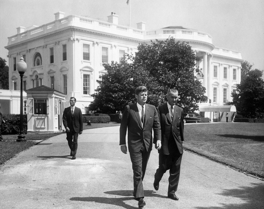 President John F. Kennedy and Vice President Lyndon B. Johnson walk across the South Lawn driveway at the White House in Washington, D.C. to attend a ceremony marking the 50th anniversary of the first state Workmen's Compensation Law, enacted in Wisconsin in 1911. Secret Service Agent Bob Lilley follows.