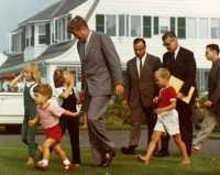 President John F. Kennedy, children and aides walk across the lawn at the Kennedy compound.